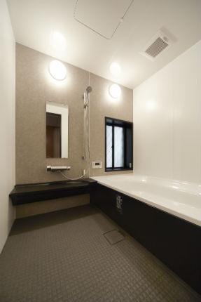 ピエトラアズールのアクセントパネルを使用したモノトーンでシックな浴室