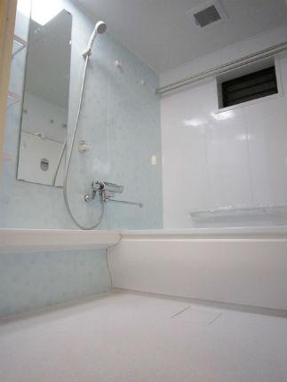 淡いブルーのアクセントパネルで明るいバスルーム