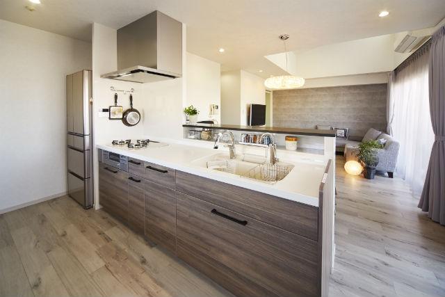 リビングと調和したウォルナット柄の対面キッチン