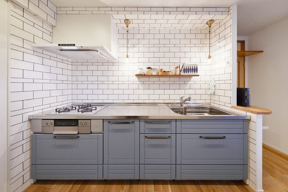 リビングと統一感のあるブルーの框扉が印象的なキッチン空間