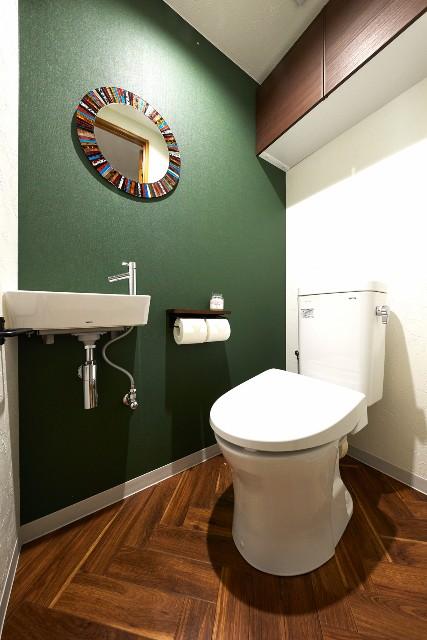 深みのある緑と濃い木目が織りなす上品なトイレ空間