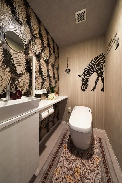 モノトーンのリーフ柄とブラウンでまとめたモダンなトイレ空間