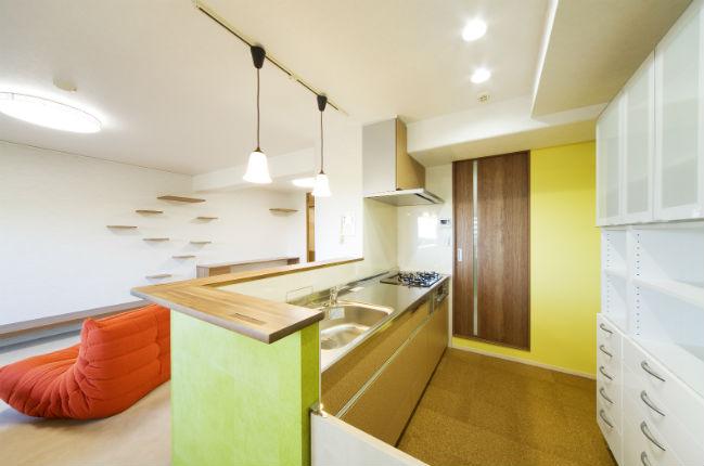 コルクタイルの床に合わせたチップウッド柄のキッチン