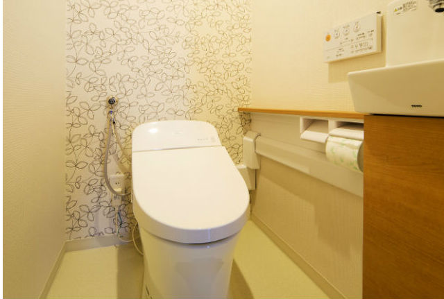 リーフ柄のアクセントクロスでリラックスできるナチュラルなトイレ