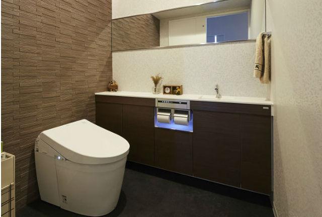 オーダーメイドのミラーの設置で広々としたモダンなトイレ
