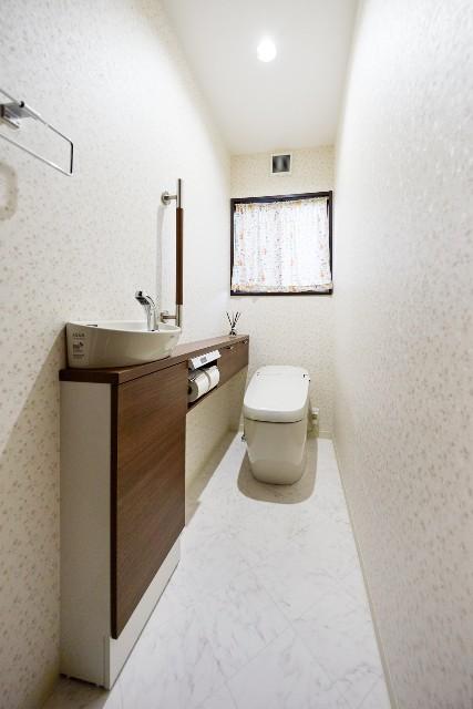 ダークブラウンと明るい小花柄のコントラストが美しいトイレ空間