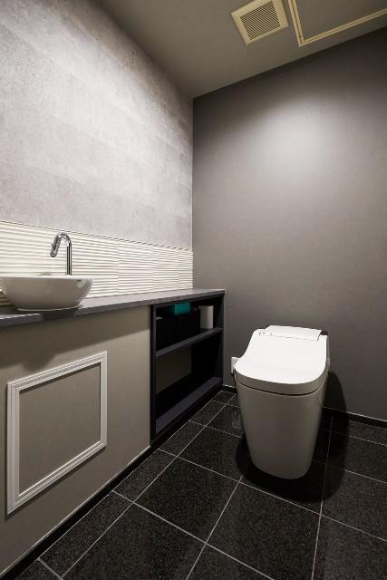 グレーの造作カウンターが映えるモノトーンなトイレ空間