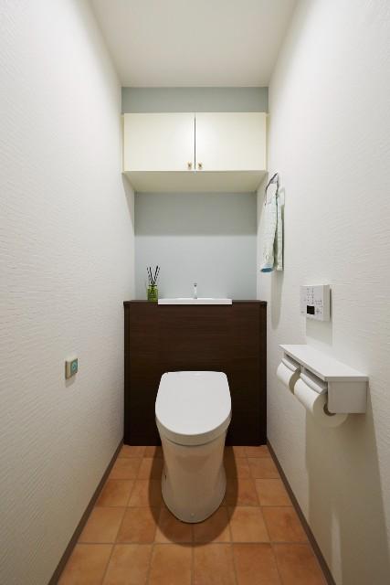 ブルーグレーのアクセントクロスが柔らかい印象を与えるトイレ