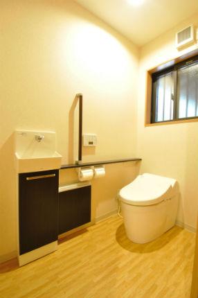 ダークウッドのカウンターと手すりで立ち座りがしやすいトイレ